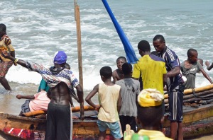 "Men and boys working on a fishing boat outside the ""Door of No Return"" at Cape Coast, Ghana"