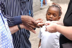 Congo girl watching a man receive a bandage